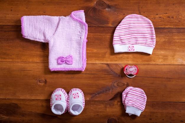 Детская одежда и аксессуары на коричневом деревянном фоне стола, плоская планировка Premium Фотографии
