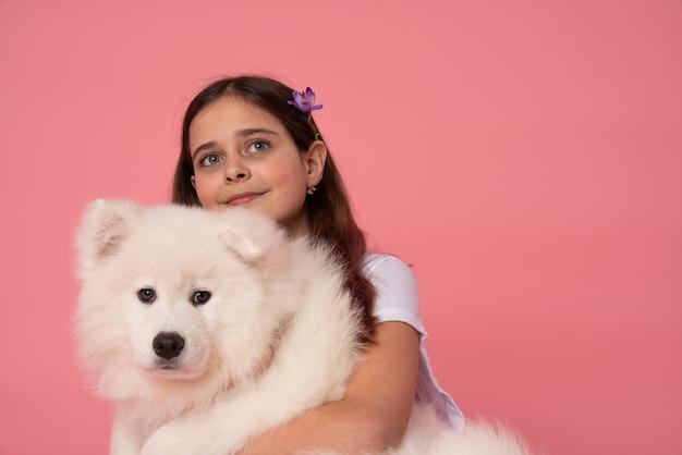 Красивая маленькая брюнетка с весенним цветком в волосах обнимает белого щенка самоеда и смотрит на розовый Premium Фотографии