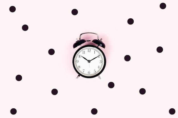 ピンクのテーブルの時計。 Premium写真