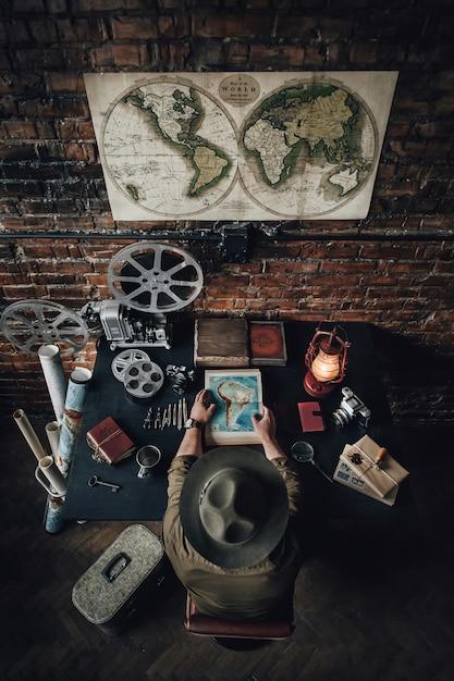 若い男が世界地図他の旅行アクセサリーを使用して休暇を計画しています。 Premium写真