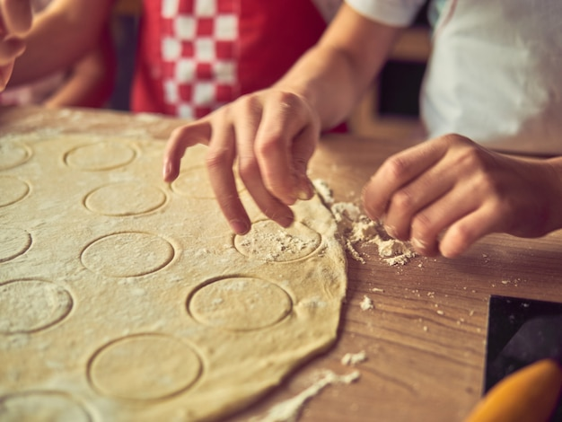 自宅のキッチンで一緒に料理をする小さな娘。幸せな家族とライフスタイルのコンセプト。 Premium写真