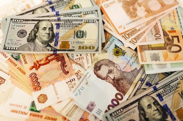 Пачка денег из разных стран на столе. доллары, евро, гривны, российские рубли, курс обмена. Premium Фотографии