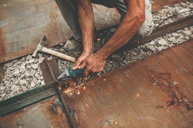 Мужчина режет железо на улице. Premium Фотографии