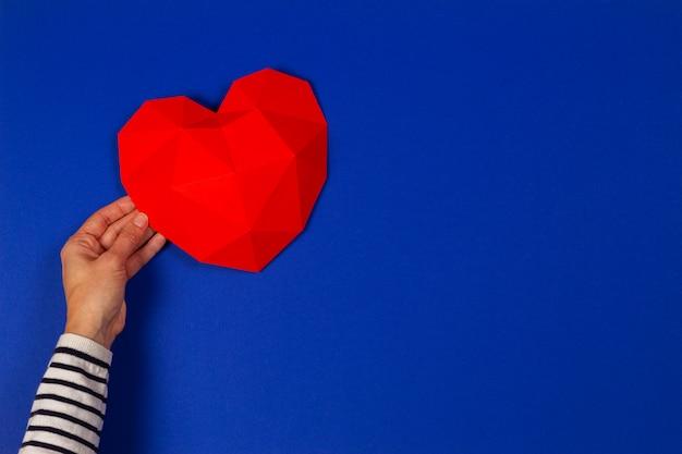 青の背景に赤の多角形の心を持っている女性の手。上面図 Premium写真