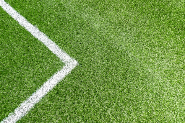 Спортивная площадка для футбола с зеленой искусственной травой и белой угловой полосой Premium Фотографии