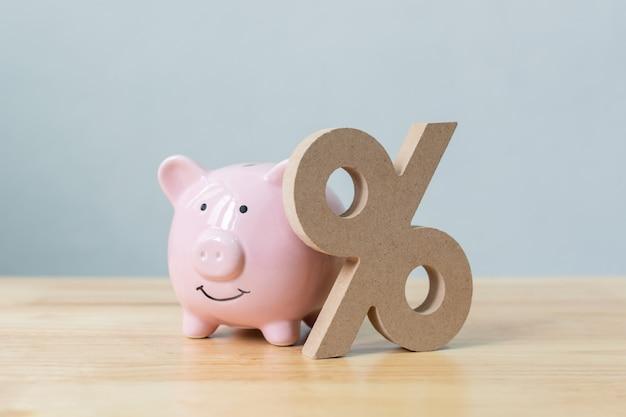 貯金とパーセント記号の木製テーブルの上のシンボル Premium写真