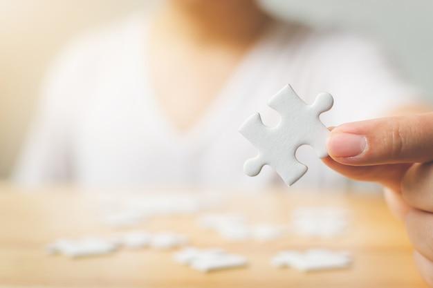 木製のテーブルに白いジグソーパズルのピースを接続しようとしている男性の手 Premium写真