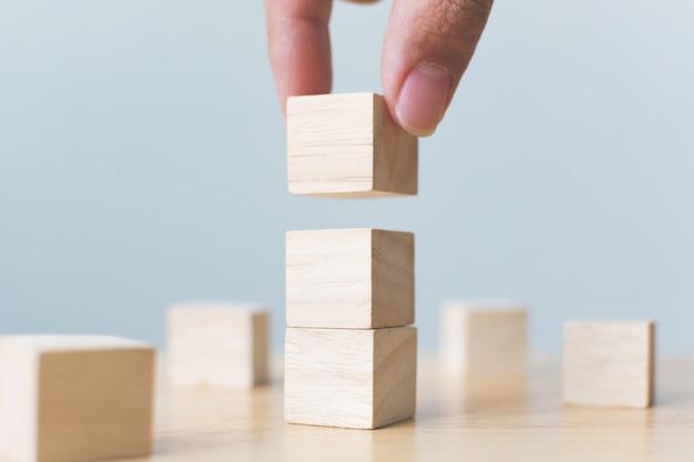Рука аранжируя деревянный блок штабелируя на верхней части с деревянным столом. Premium Фотографии