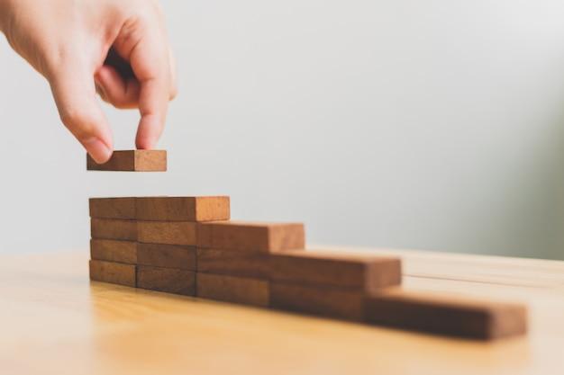 ステップ階段として積み重ねる木ブロックを手配。ビジネス成長成功プロセスのためのはしごのキャリアパスの概念 Premium写真