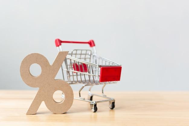 パーセンテージ記号シンボルアイコン木製と木製のテーブルの上のショッピングカート Premium写真
