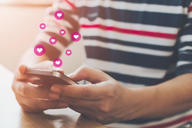 ソーシャルネットワークの共有とオンラインコミュニティでのコメント、スマートフォンを持っているとアイコンの心を持つアプリケーションソーシャルメディアを使用している人間の手 Premium写真