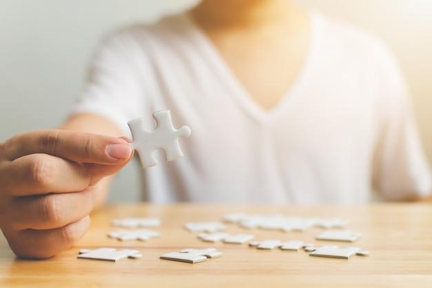 Рука мужчины, пытаясь соединить кусочки белой головоломки на деревянный стол Premium Фотографии