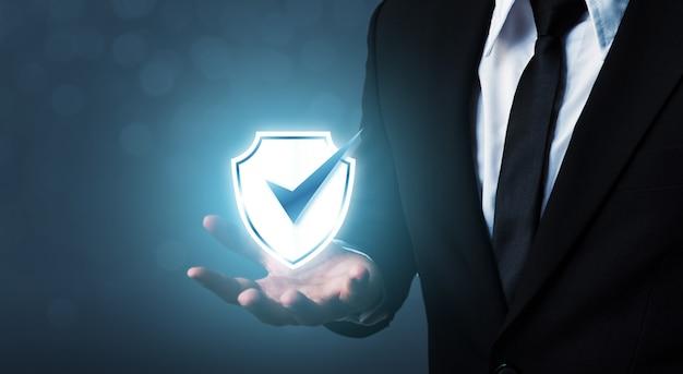 Бизнесмен держит щит защитить значок Premium Фотографии