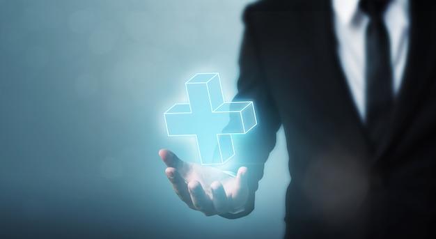Бизнесмен рука держит знак плюс виртуальные средства, чтобы предложить положительное (например, преимущества, личностное развитие, социальная сеть) Premium Фотографии