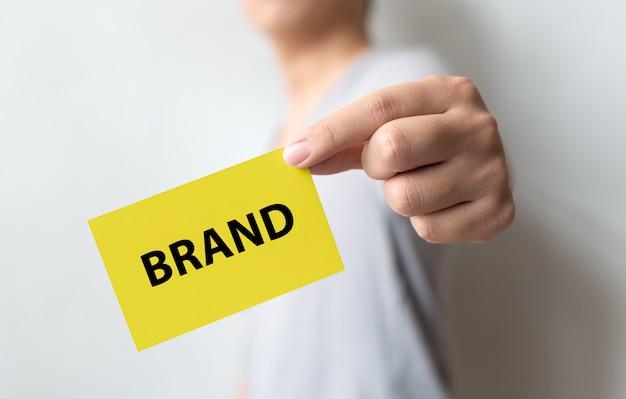 Человек, держащий желтую карточку и слово бренд. создание бренда для концепции успеха Premium Фотографии