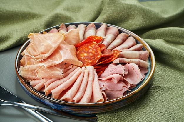 Роскошные итальянские мясные закуски для вина в керамической пластине на деревянный стол. салями, ветчина, прошутто и чоризо. крупным планом, селективный фокус Premium Фотографии
