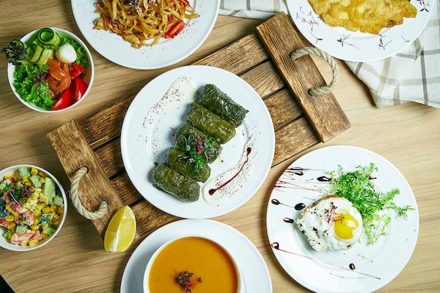 料理がたくさんあるダイニングテーブル:ドラマ、野菜サラダ、スープ、卵とデザートのビーフステーキ。トップビュー、食品フラットレイアウト Premium写真