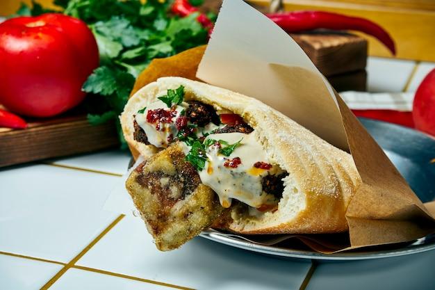 おいしいビーガンストリートフード-ファラフェル、タマネギ、ソース、白いテーブルの上のピタ。ギリシャ料理。見る。 Premium写真