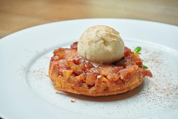 Свежеиспеченный яблочный пирог из песочного теста с шариком мороженого на белой тарелке на деревянном столе. вкусная выпечка на завтрак Premium Фотографии