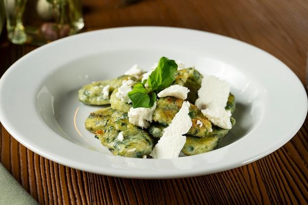 グリーンニョッキ、バジル、ほうれん草、ペストフェタチーズ、グリーンクロスとオリーブオイル。 Premium写真