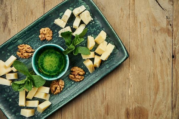 前菜-チーズプレート。セラミックプレートの異なる自家製チーズ-ブリー、カマンベール、蜂蜜とナッツを使ったオランダ料理。ワイン前菜。 Premium写真