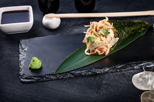 カニとトビコキャビア添えのおいしい手巻き寿司のクローズアップを醤油と生姜の暗い石のプレートで提供しています Premium写真