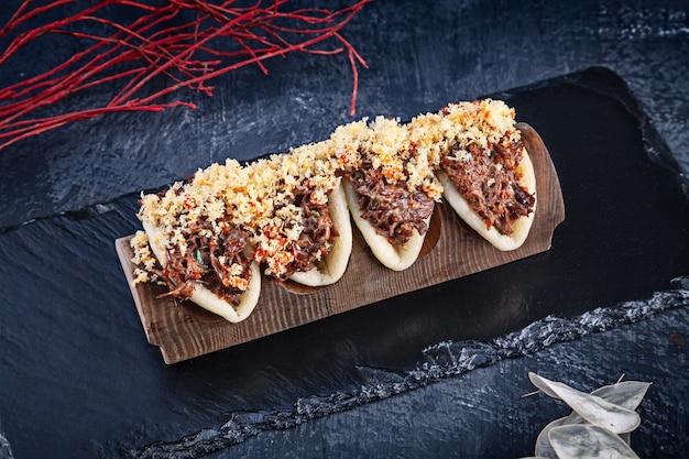 グアバオ、肉入りのまんじゅう(皮)のクローズアップ。バオは、暗い背景においしいトッピングを添えてください。アジア料理。アジアンサンドイッチ蒸しグアバオ。和風ファーストフード Premium写真
