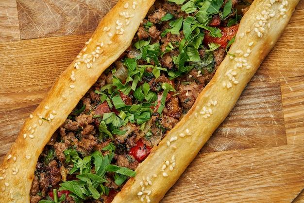 Пиде - турецкое блюдо в форме тортильи с говяжьим или мясным ягненком и зеленым луком на деревянном подносе. восточная пицца, рецепт или меню Premium Фотографии