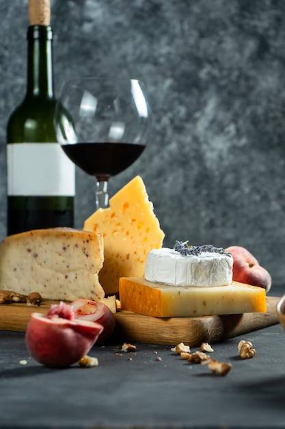 赤ワインとチーズ。まな板の上のナッツ、ラベンダー、イチジクの桃とさまざまな種類のチーズ。ロマンチックなディナー。デザインのスペースをコピーします。暗い背景。ソフトフォーカス Premium写真