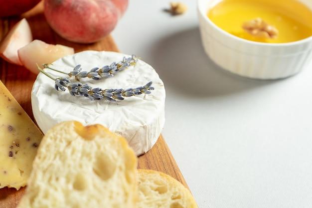 Разные виды сыров на деревянной разделочной доске. сыр с инжирным персиком, медом, чиабаттой и орехами, стакан красного вина. стильная еда квартира лежала на сером фоне. копировать пространство мягкий фокус Premium Фотографии