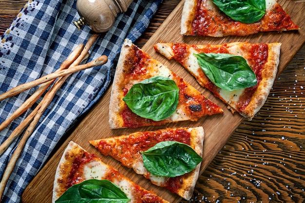 木製のまな板の背景にスライスしたマルガリータピザの平面図です。デザインのコピースペースの刈り取らピザ。メニューの写真、イタリア料理 Premium写真