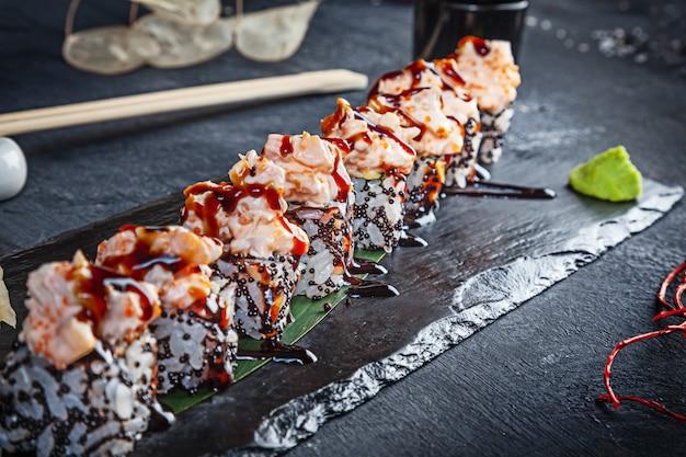 ロール寿司のセットのビューを閉じます。暗い背景に黒い石の上にうなぎとエビのロールします。日本料理。コピースペース。メニューには寿司を提供しています。健康食品・シーフード Premium写真