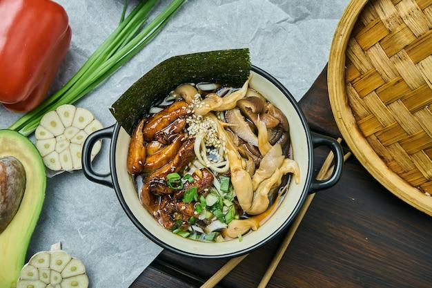 Классический азиатский суп с лапшой удон, нори, грибами шиитаке и жареной на воке курицей в черном шаре на деревянном столе с копией пространства. вид сверху, плоская кладка еды Premium Фотографии