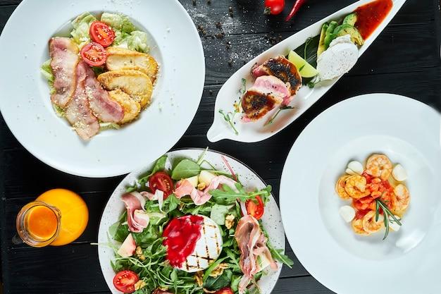 さまざまな料理のディナーテーブル-シーザーサラダ、マグロステーキ、エビのスープ、焼きカマンベールサラダ Premium写真