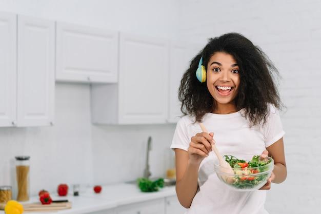 キッチンでベジタリアンディナーを調理する美しいアフリカ系アメリカ人女性を興奮させた。新鮮なサラダとフクロウを押し、自宅で音楽を聴く、笑って幸せな感情的な女の子 Premium写真