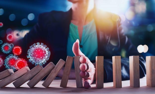 実業家は、ドミノゲームのようなウイルスによる連鎖落下を阻止します。ビジネスの危機と失敗を防ぐ概念。 Premium写真
