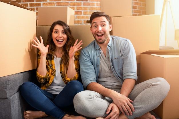 Счастливая пара нашла новый дом и им нужно оформить все посылки. концепция успеха, перемен, позитива и будущего Premium Фотографии
