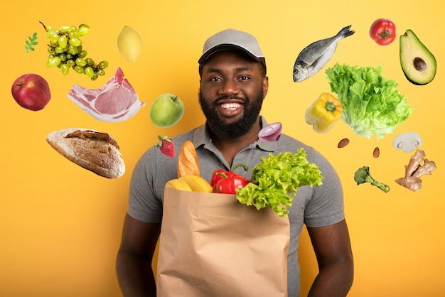 食物と一緒にバッグを届ける準備ができて幸せな表情の配達員。黄色の背景。 Premium写真