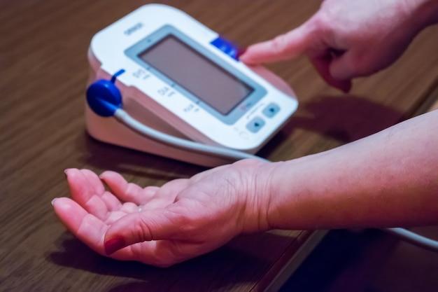 Женщина заботится о здоровье с монитором ритма очага и кровяным давлением Premium Фотографии