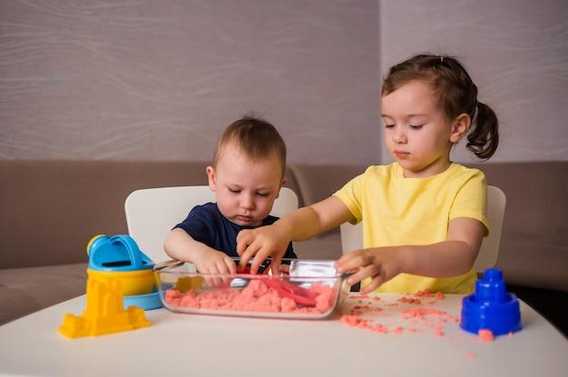 Брат и сестра играют за столом с кинетическим песком. сенсорные игры дома. Premium Фотографии