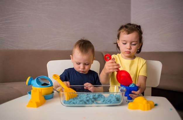 Брат и сестра играют с песком за столом в комнате. игры с кинетическим песком. Premium Фотографии
