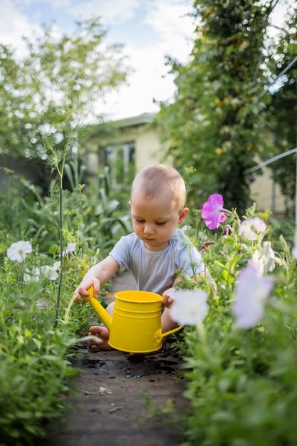 小さな男の子が黄色のじょうろで庭に座っています。 Premium写真