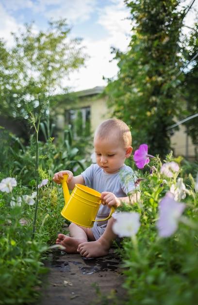小さな男の子が座って庭に黄色のじょうろを持っています。 Premium写真