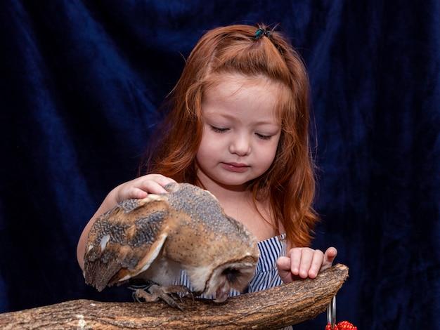 Красивая рыжеволосая женщина фотографирует с ее любимой совой Premium Фотографии