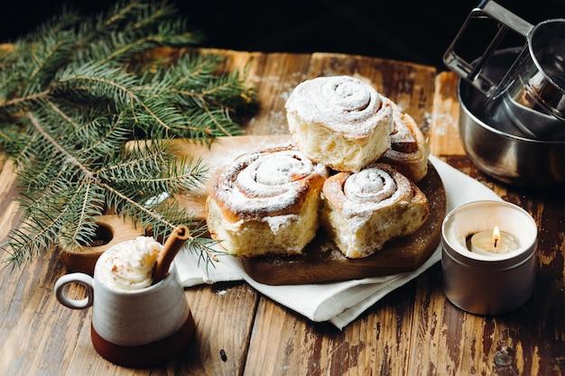 Свежеиспеченные рождественские булочки с порошком и горячим какао с палочкой корицы на деревенский праздничный стол. Premium Фотографии