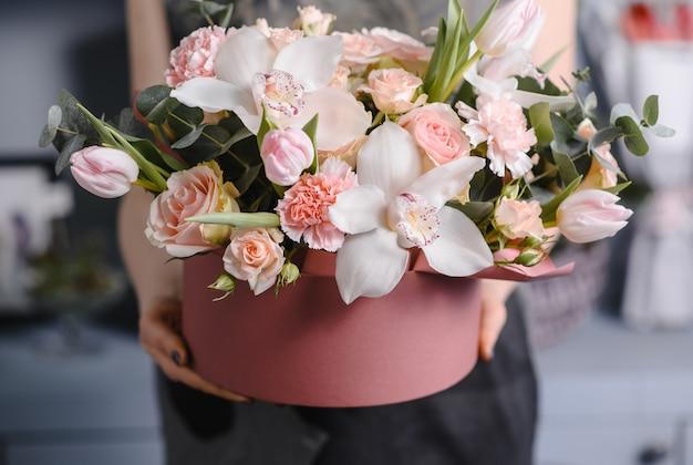 紫色のカーネーションとマティオラと大きくて美しいカラフルな花のウェディングブーケを保持している非常に素敵な若い女性 Premium写真