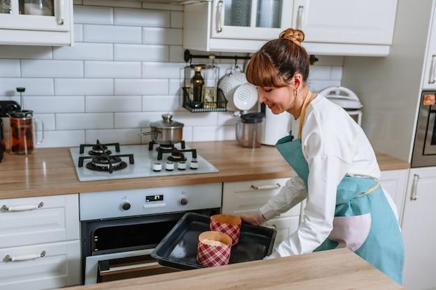 Женщина-повар готовит положить формы с куличами в духовку Premium Фотографии