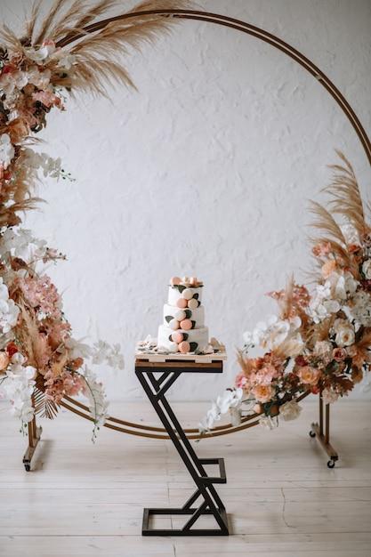 Трехъярусный свадебный торт на подставке на фоне арки Premium Фотографии