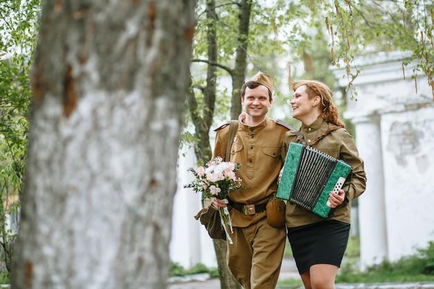 Солдат идет по аллее, обнимая военную женщину, играющую на аккордеоне Premium Фотографии