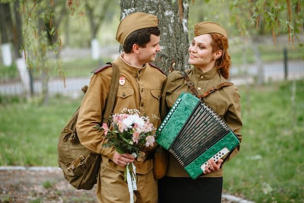Солдат обнимает военную женщину, играющую на аккордеоне Premium Фотографии